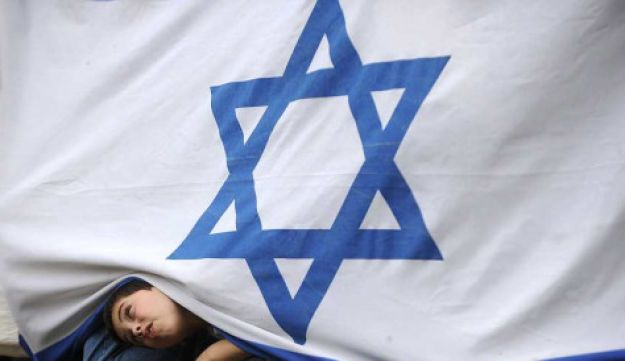 A boy peering from under an Israeli flag