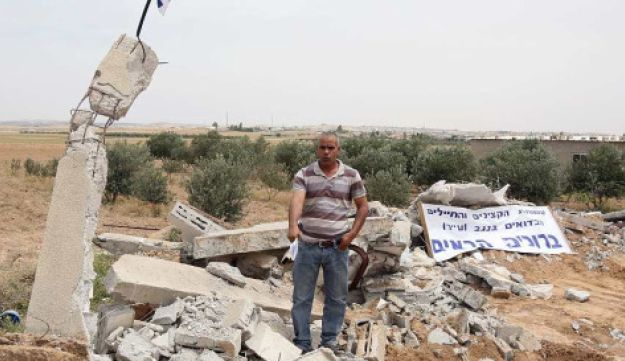 A man stands amid the ruins of a Bedouin clubhouse demolished by the IDF, April 21, 2010