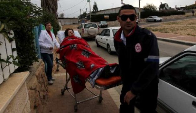 Paramedics treat woman suffering from shock after a Grad rocket hit Be'er Sheva on March 23, 2011