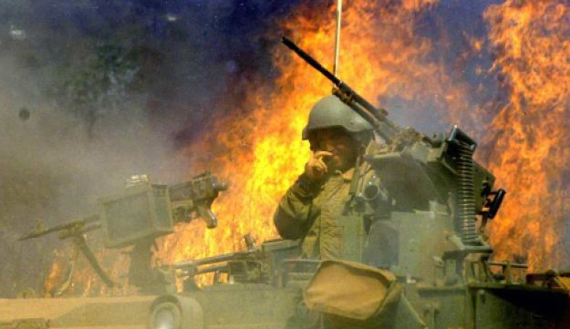 Israeli soldiers withdrawing from Lebanon at the end of the Second Lebanon War in 2006. A helmeted soldier in a military vehicle with machine guns is in the foreground of the photograph, The background is a blaze of bright-orange flames and of smoke.