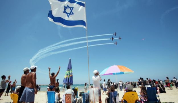 Spectators cheering the Air Force Independence Day flyover above a Tel Aviv beach.