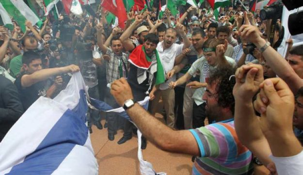 Protesters burn an Israeli flag during a demonstration
