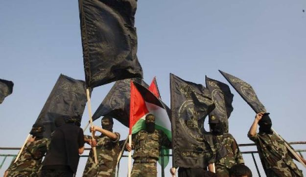 Islamic Jihad militant wave flags during a rally marking Nakba Day in the central Gaza Strip