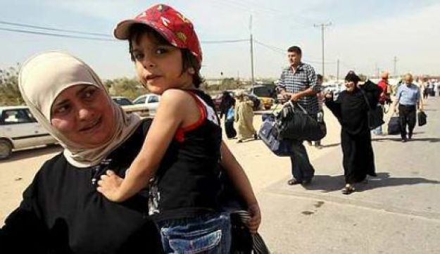 A Palestinian woman carrying her daughter arrives at the Rafah border crossing in the southern Gaza