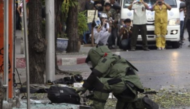 A Thai Explosive Ordnance Disposal (EOD) official examines a backpack that was left on the bomb site