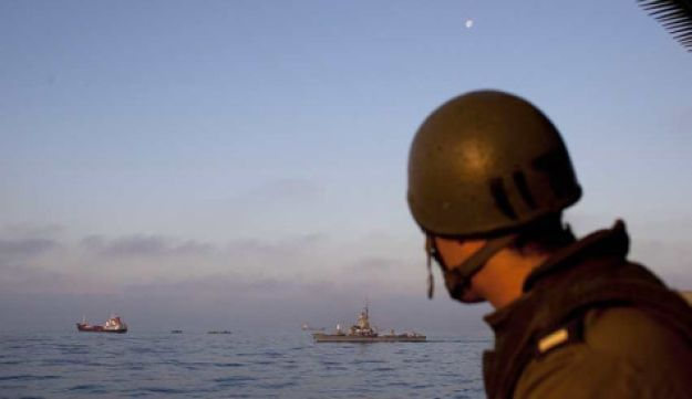 An IDF oldier stands guard aboard a naval vessel as Gaza-bound ships are intercepted