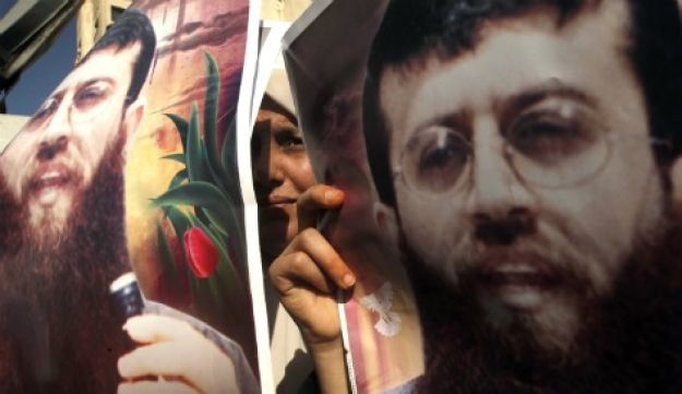 Palestinians hold pictures of Khader Adnan, a jailed senior member of Islamic Jihad.