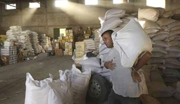 A Palestinian man carries a sack of wheat inside a shop in northern Gaza Strip June 8, 2010.