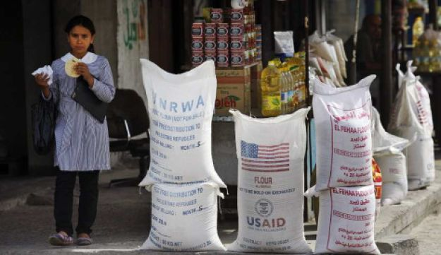 A Palestinian girl stands by sacks of humanitarian aid in Shatie refugee camp, in Gaza