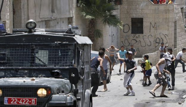 Palestinian youths throw stones at Israeli military vehicle in East Jerusalem