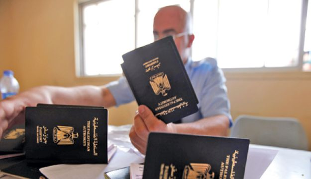 A Hamas policeman checks passports at Rafah
