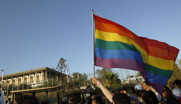 Participants walk near the Knesset, the Israeli parliament, during a gay pride parade in Jerusalem.