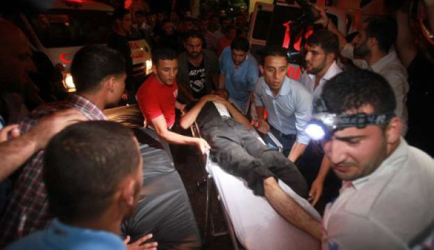A wounded Palestinian is carried into Al-Shifa hospital