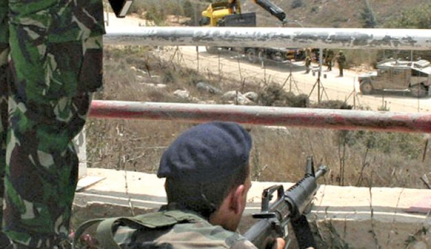 A Lebanese soldier holding his rifle as Israeli troops patrol the border fence in the southern Leban