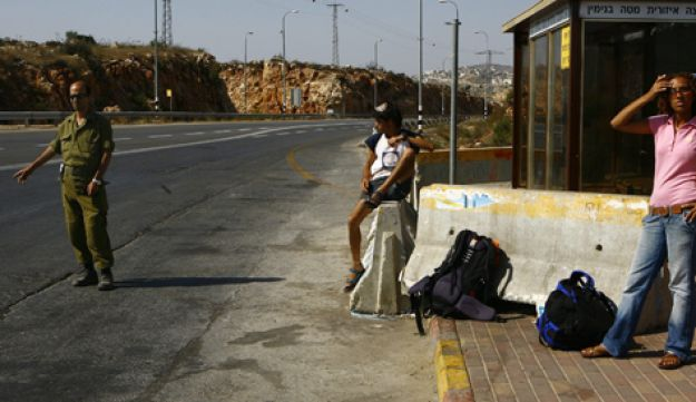 Israelis hitchhiking at a 'trempiada' near the West Bank settlement of Ofra.