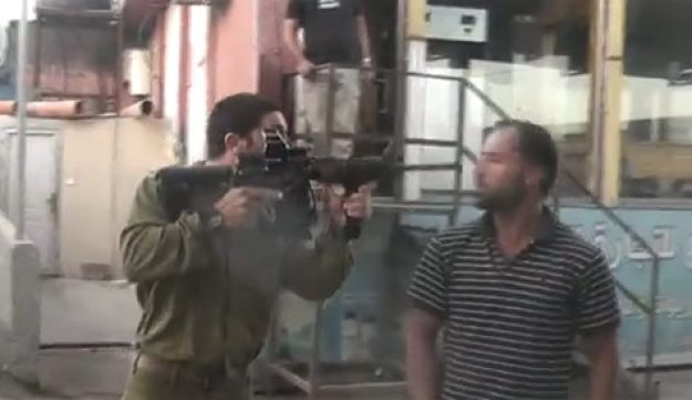 IDF officer pointing gun at Palestinian - YouTube - July 20, 2011.