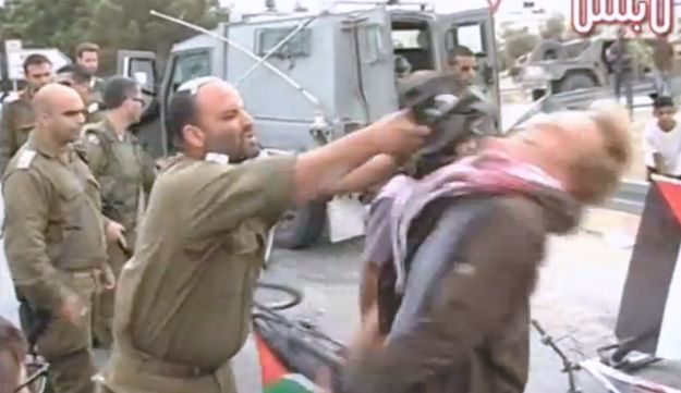 YouTube image grab of IDF soldier hitting leftist activist with M-16