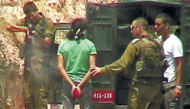 An IDF soldier shooting a bound Palestinian in the foot with a rubber bullet.