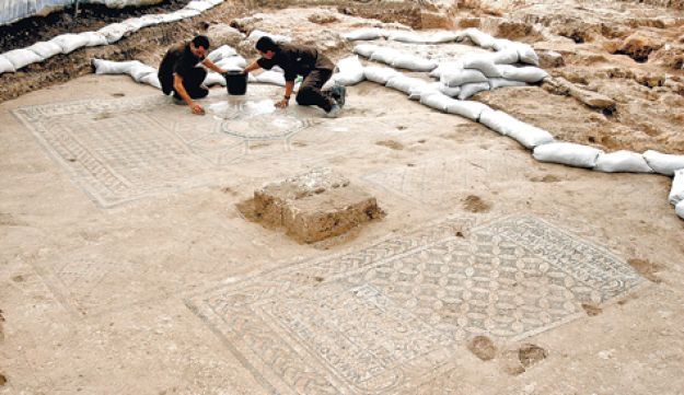 Convicted felons clearing a mosaic uncovered within the confines of Megiddo Prison.