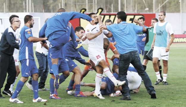 Players from Hapoel Ramat Gan and Bnei Lod exchanging blows during a brawl following a soccer match