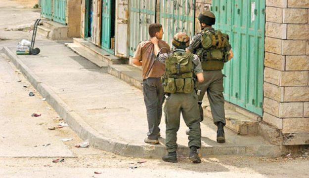 Soldiers detain a Palestinian teenager in Hebron, April 2010