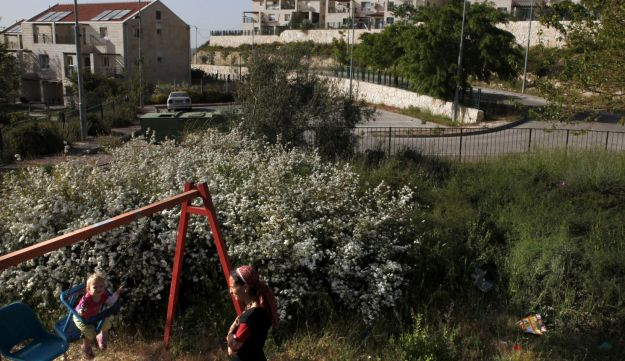 An Israeli settler plays with her child at a playground in Beit El settlement, April 22, 2012