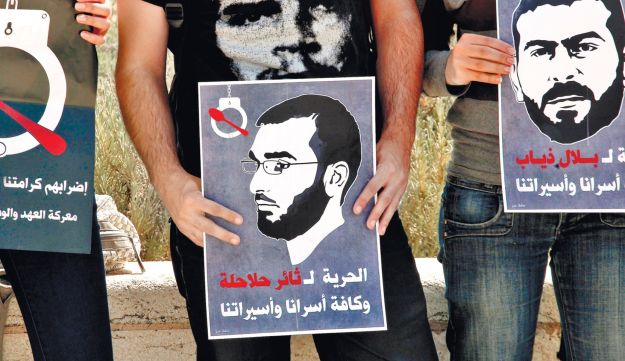 A protester holding a poster of a Palestinian prisoner who is on hunger strike in Israeli prison.