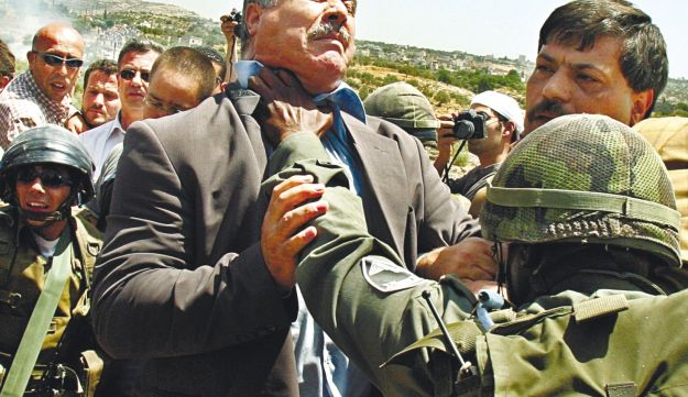 Mohammed Barakeh getting throttled by IDF soldier in Bil'in in 2005.
