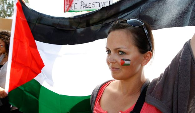 A woman hold a Palestinian flag during a protest to show solidarity with Palestinians.