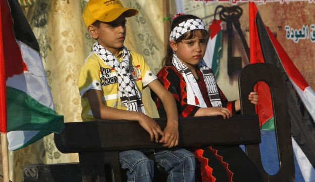 Palestinian children hold a key to commemorate Nakba day.