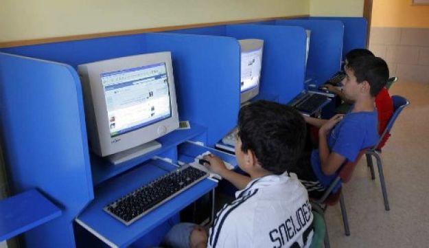 Palestinian boys look at websites on the Internet in the West Bank city of Bethlehem.