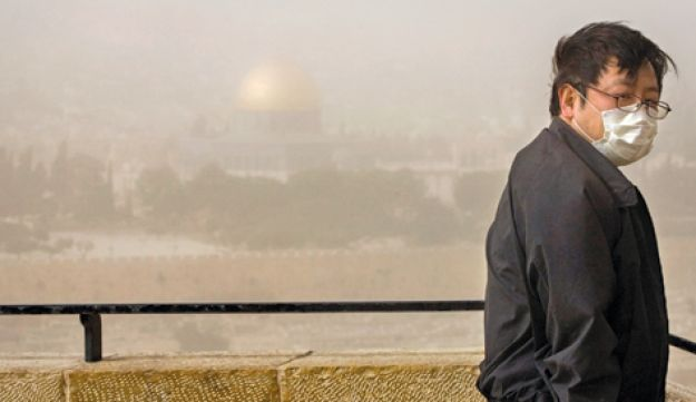 A tourist looking out over smog-covered Jerusalem (Olivier Fitoussi)