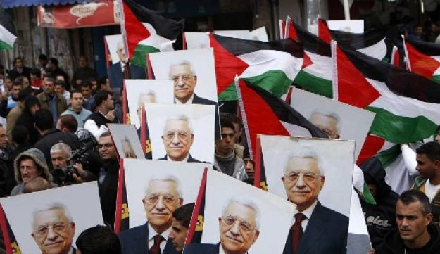 Palestinians hold flags and posters of Palestinian President Mahmoud Abbas