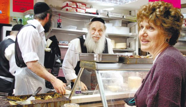 Joan Nathan speaking with workers at Bnei Brak's Muchan Umezuman deli.