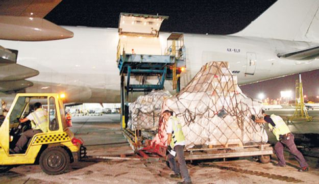 Workers at Ben-Gurion Airport loading a jumbo jet with supplies for Turkey - Hadar Cohen