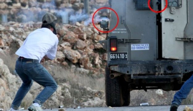 Palestinian protester Mustafa Tamimi, just before he was hit by a tear-gas canister in the West Bank village of Nabi Saleh, December 9, 2011. Rifle barrel and canister circled in red.