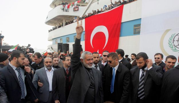Hamas leader Ismail Haniyeh flashing a victory sign in front of the Mavi Marmara in Istanbul, 2012.