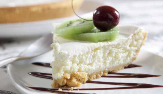 Breakfast cheesecake, decorated with kiwi fruit and cherry.