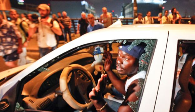 African migrants with car windows shattered by demonstrators in South Tel Aviv, May 23, 2012.