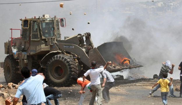 Palestinians throw rocks at an Israeli army bulldozer during clashes in the northern West Bank .