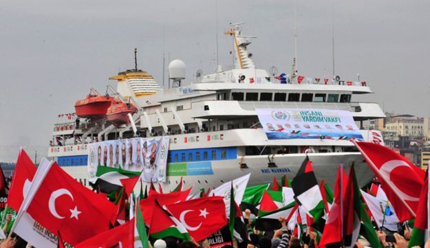 Pro-Palestinian activists wave Turkish and Palestinian flags welcoming the Marmara.