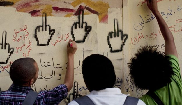 Youth activists write graffiti on a wall in Tahrir Square in central Cairo, Egypt, May 24, 2012.