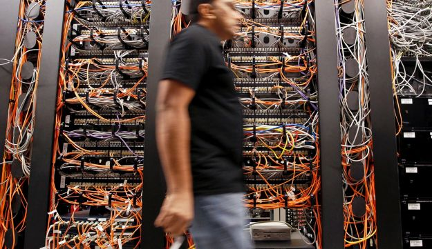 A man walks by computer network servers in California.