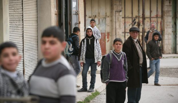 Palestinian children in Hebron looking on as Shovrim Shtika lead a tour of the city.