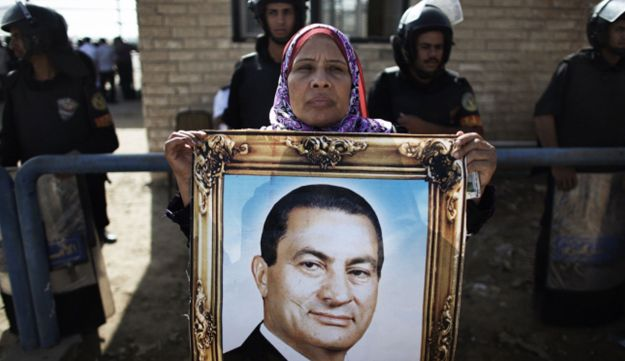 An Egyptian woman holds a portrait of former president Hosni Mubark outside the court in Cairo.