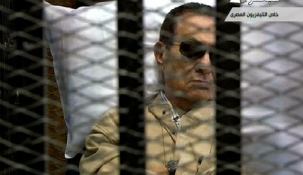 An image grab taken from Egyptian state TV shows ex-Egyptian president Mubarak sitting in court .