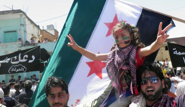 Syrians waving flag in Houla - AFP - June 7, 2012