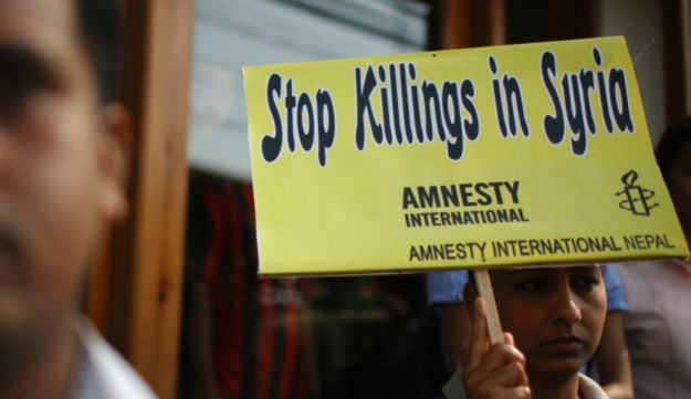 An activist with a placard participates in a sit-in protest outside the United Nations office