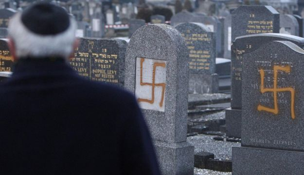 Francis Levy, head of the North Alsacian Jewish community, inspects tombstones desecrated by vandals