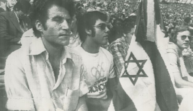 Israelis with a black-crepe covered Israeli flag sit in the Munich Olympic Stadium on Sept 6, 1972